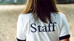 "Woman wearing ""staff"" shirt"